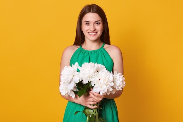 Halve lengte dame in elegante groene jurk houdt boeket bloemen in handen op geel, blij om pioenen te ontvangen als presenmt.