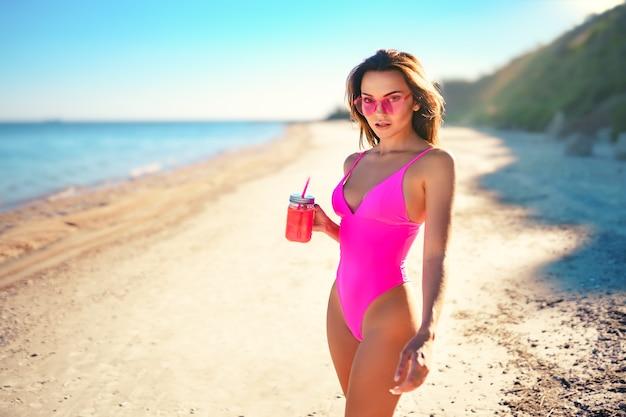 Halve lengte jonge vrouw in bikini met smoothies op het strand detox concept perfect lichaam
