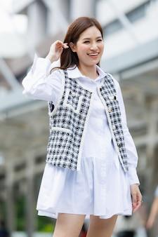 Halve lengte lichaamsportret van schattige lachende jonge volwassen aziatische vrouw met een lang bruin kapsel en modieuze witte en zwarte kleding en hoge hakken, staande op de trap en kijkend naar de camera