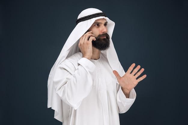 Halve lengte portret van arabische man op donkerblauwe studio
