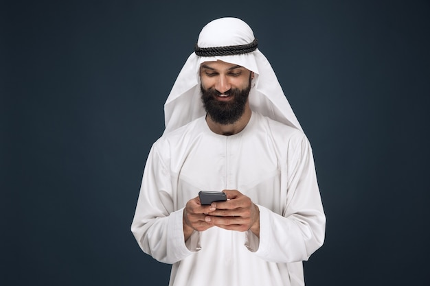 Halve lengte portret van arabische saoedische man op donkerblauwe studio achtergrond. jonge mannelijke model met behulp van smartphone, chating. concept van zaken, financiën, gezichtsuitdrukking, menselijke emoties, technologieën.