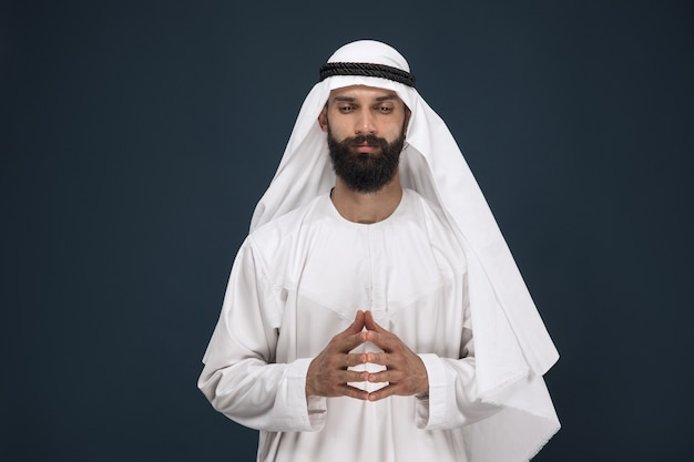 Halve lengte portret van arabische saoedische zakenman op donkerblauwe studioachtergrond. het jonge mannelijke model bidt en kijkt attent. concept van zaken, financiën, gezichtsuitdrukking, menselijke emoties.