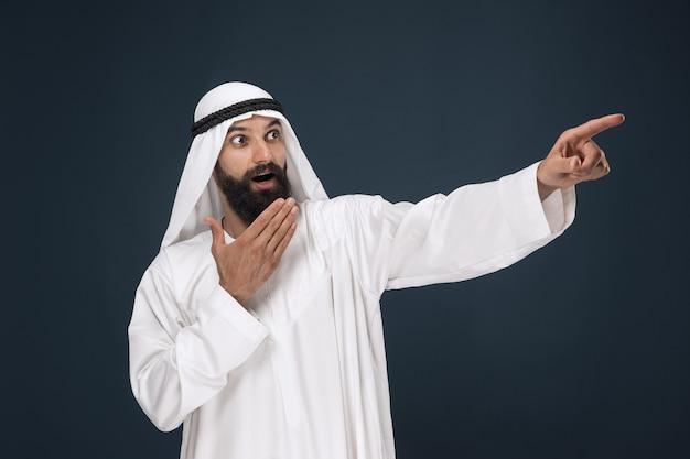 Halve lengte portret van arabische saoedische zakenman op donkerblauwe studioachtergrond. jong mannelijk model verbaasd, wijzend of kieskeurig. concept van zaken, financiën, gezichtsuitdrukking, menselijke emoties.