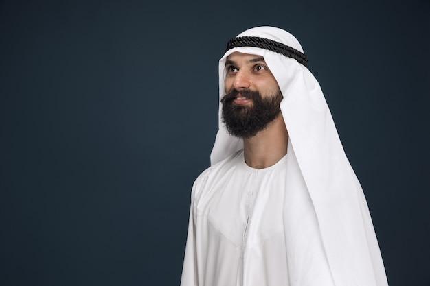 Halve lengte portret van arabische saoedische zakenman op donkerblauwe studiomuur