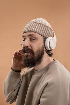 Halve lengte portret van blanke man met bril en hoed geïsoleerd over lichtgele muur. snor en baard. concept van menselijke emoties, gezichtsuitdrukking, advertentie, mode. ruimte kopiëren