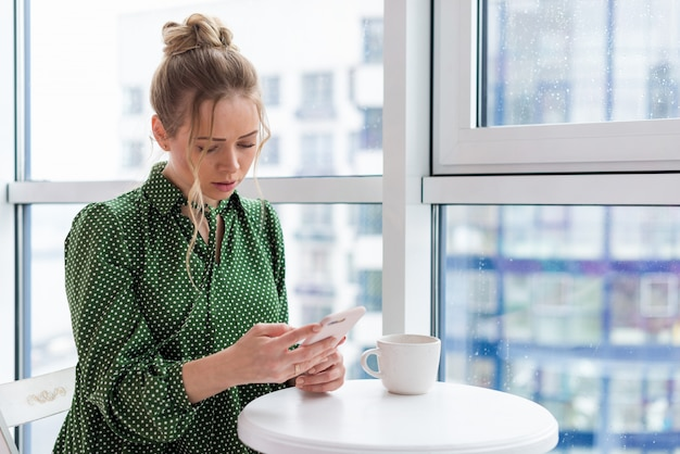 Halve lengte portret van blond meisje zit aan de tafel naast het raam met een mobiele telefoon en kijken naar het scherm