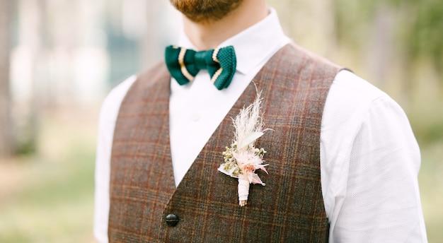 Halve lengte portret van bruidegom in wit overhemd, groene vlinderdas en bruin vest