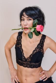 Halve lengte portret van een meisje in zwarte lingerie met een roos in haar tanden