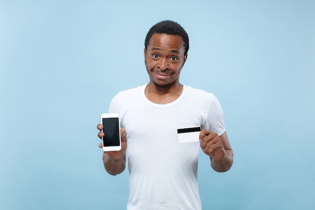 Halve lengte portret van jonge afro-amerikaanse man in wit overhemd met een kaart en smartphone op blauwe ruimte