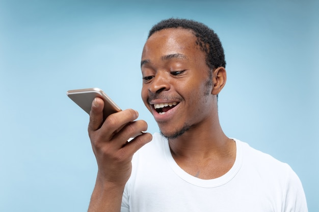 Halve lengte portret van jonge afro-amerikaanse man in wit overhemd op blauwe achtergrond. menselijke emoties, gezichtsuitdrukking, advertentie, verkoopconcept. een smartphone vasthouden, praten of een spraakbericht opnemen.