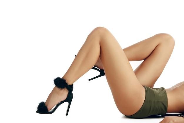 Halve lengte portret van jonge mooie vrouw met perfect lichaam en goed onderhouden huid. het dragen van shirt en beha.