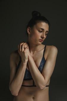 Halve lengte portret van jonge trieste vrouw in ondergoed op donkere muur. verdriet, depressie en verslaving. concept van menselijke emoties, feminisme, problemen en rechten van de vrouw, geestelijke gezondheid.