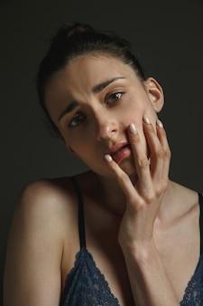 Halve lengte portret van jonge trieste vrouw in ondergoed op donkere studiomuur