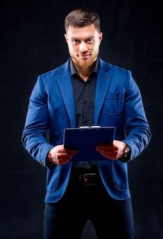 Halve lengte portret van knappe jonge lachende man met donker shirt en blauw pak met blauwe map