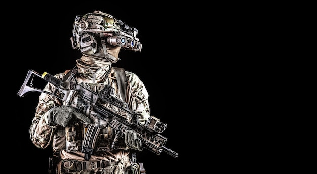 Halve lengte portret van leger special forces schutter, commando elite soldaat uitgerust radio tactische headset, gewapende dienst geweer, met behulp van nachtkijkers in duisternis, geïsoleerd op zwart, copyspace