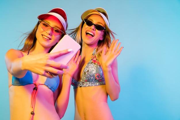 Halve lengte portret van mooie jonge meisjes geïsoleerd op blauwe studio achtergrond in neonlicht. vrouwen poseren in modieuze romper. gelaatsuitdrukking, zomer, weekendconcept. trendy kleuren.