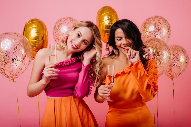 Halve lengte portret van twee jonge dames die champagne drinken