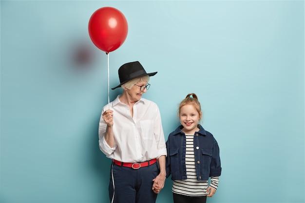 Halve lengte shot van aanhankelijke oma feliciteert klein kind met de eerste dag op school, houdt rode ballon met blije uitdrukkingen. vrolijke oma, kleindochter komt in een goed humeur terug van circusvoorstelling