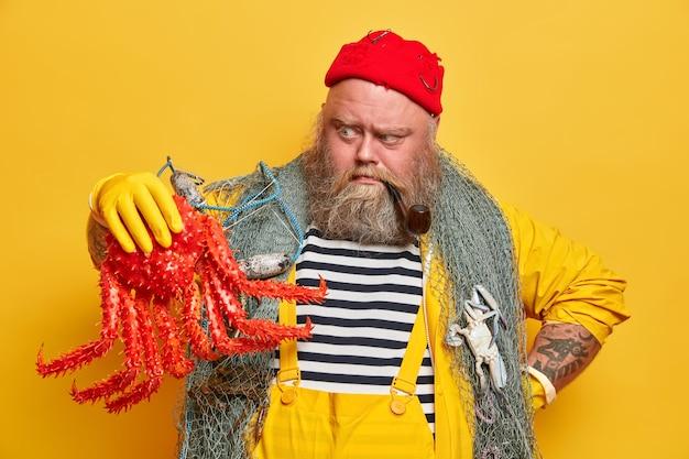 Halve lengte shot van bebaarde stevige visser kijkt met vreemde uitdrukking naar gevangen grote octopus, weet niet wat ermee te doen