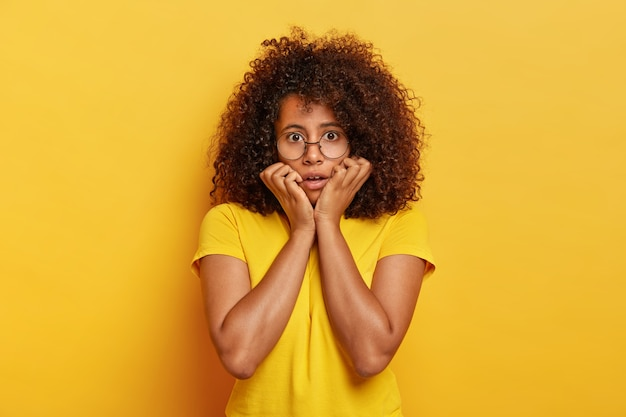 Halve lengte shot van beschaamd meisje met afro kapsel, kijkt met schrik naar de camera, houdt kin, draagt optische bril en helder geel t-shirt, vormt binnen