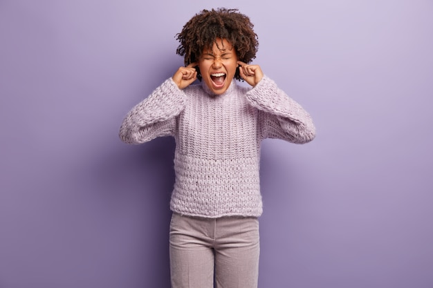 Halve lengte shot van depressieve vrouw van gemengd ras sluit oren, wil geen ruzie horen, geïrriteerd door roddels, draagt gebreide trui en broek, staat over paarse muur. lawaai negeren