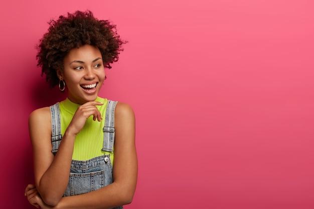 Halve lengte shot van donkere huid meisje houdt de blik opzij, houdt de hand onder de kin, draagt een denim overall, is opgewekt, poseert over een roze muur, kopieer ruimte opzij voor je promotie