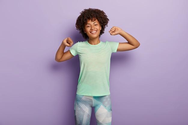 Halve lengte shot van gelukkige jonge afro-amerikaanse vrouw strekt zich uit handen, doet ochtendoefeningen met goed humeur