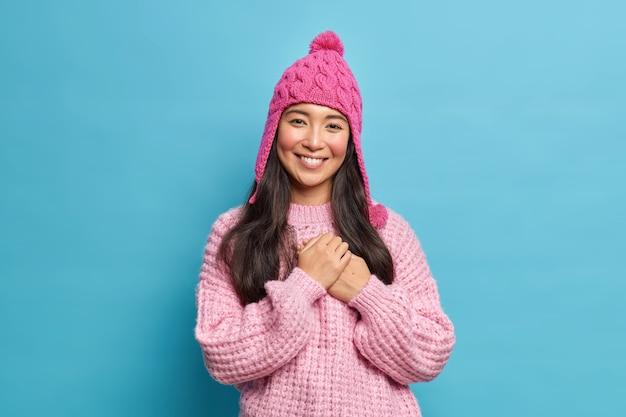 Halve lengte shot van mooie aziatische vrouw in breigoed dankbaar voor hartverwarmende woorden glimlacht poseert aangenaam tegen blauwe muur