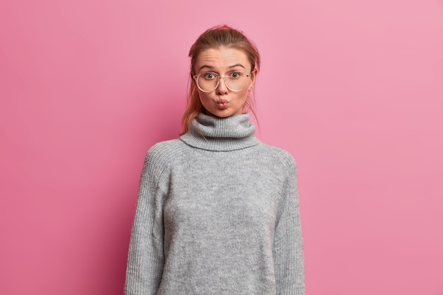 Halve lengte shot van mooie jonge vrouw houdt lippen gevouwen, grimas maakt, gaande engelse club, draagt grote optische bril en grijze trui