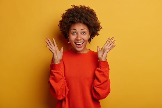 Halve lengte shot van optimistische gekrulde vrouw houdt handpalmen omhoog, gekleed in een rode trui, voelt zich opgewonden door uitstekend nieuws te horen, glimlacht breed, staat tegen een gele achtergrond.