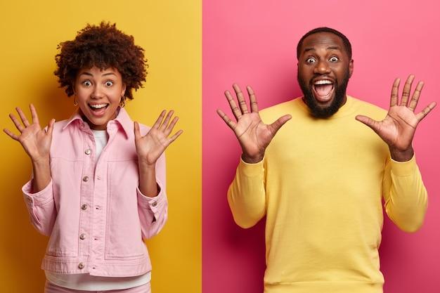 Halve lengte shot van optimistische zwarte vrouw en man heffen handpalmen op, reageren op plotselinge verrassing