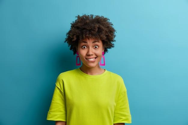 Halve lengte shot van positieve etnische vrouw reageert op verrassend nieuws, bijt op de lippen, heeft blije uitdrukking geschokt, draagt groen zomert-shirt, geïsoleerd over blauwe muur