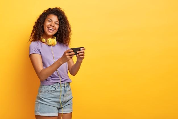 Halve lengte shot van positieve jonge vrouw met afro kapsel poseren tegen de gele muur