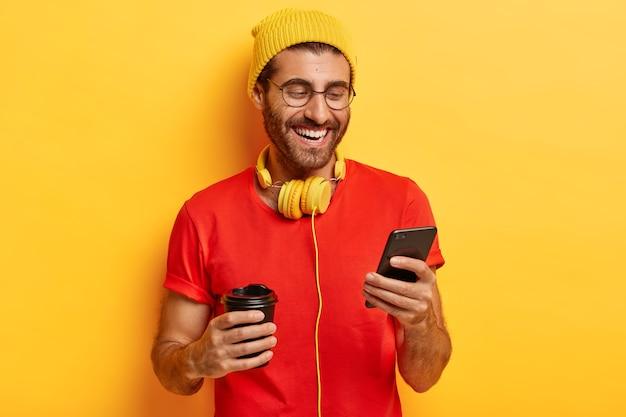 Halve lengte shot van positieve man glimlacht op het scherm van de smartphone, heeft een online gesprek in de chat, vergeet alle problemen