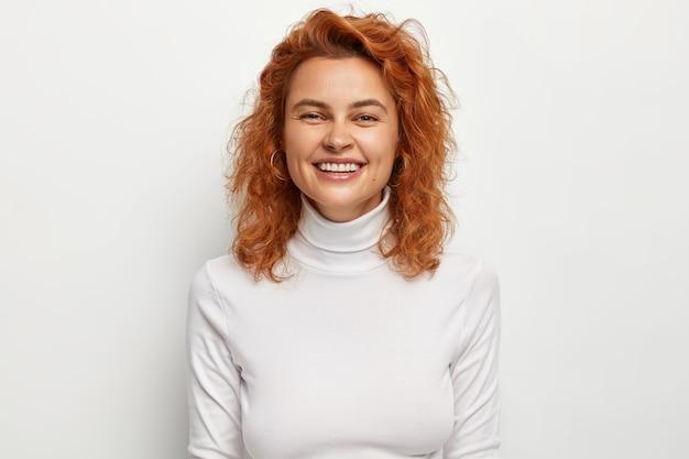 Halve lengte shot van positieve roodharige vrouw heeft een oprechte brede glimlach