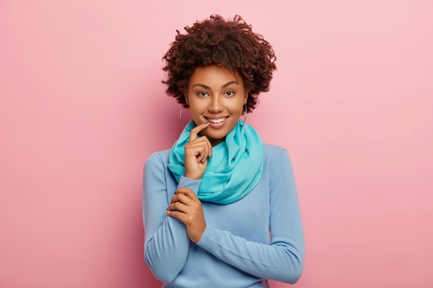 Halve lengte shot van schattige afro-amerikaanse vrouw met knapperig haar, draagt blauwe trui met zijden sjaal houdt vinger bij de lippen, ziet er mysterieus geïsoleerd uit over roze muur. emoties concept