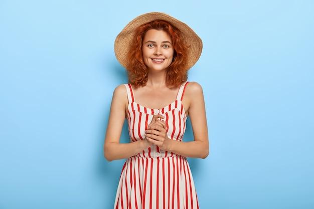 Halve lengte shot van vrij lachende vrouw met gemberkapsel, draagt strooien hoed en gestreepte jurk, klaar voor date met vriendje, houdt de handen bij elkaar, heeft tevreden gezichtsuitdrukking. zomer mode