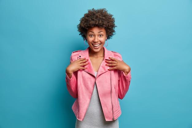 Halve lengte shot van vrij vrolijk afro-amerikaans meisje gekleed in modieuze roze jas, breed lacht, hoort spannend goed nieuws, poses