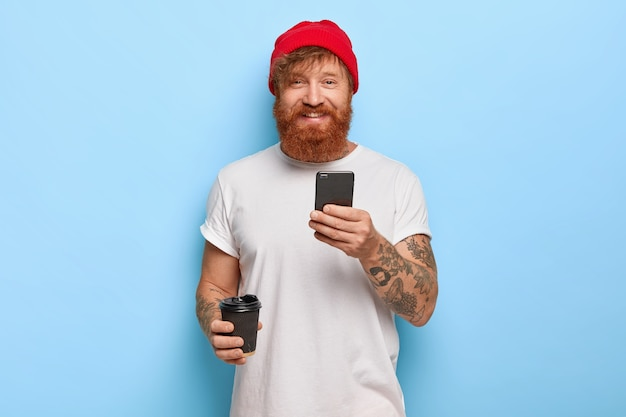 Halve lengte shot van vrolijke bebaarde roodharige man draagt stijlvolle hoed, witte casual t-shirt, houdt mobiele telefoon, koffie meenemen, in goed humeur zijn, typt berichten