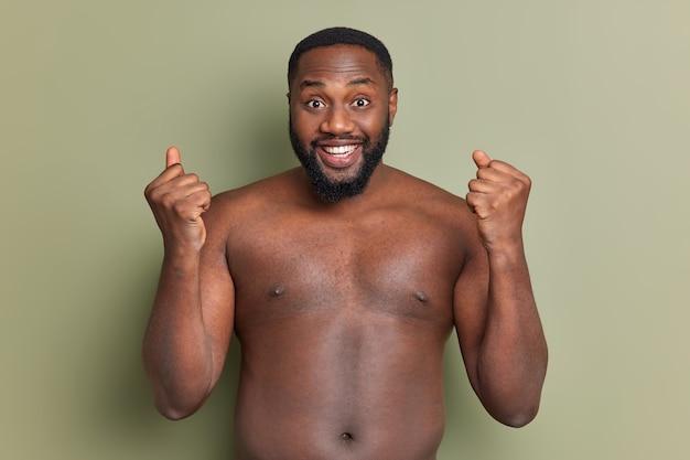 Halve lengte shot van vrolijke zwarte man viert succes balde vuisten en glimlacht breed