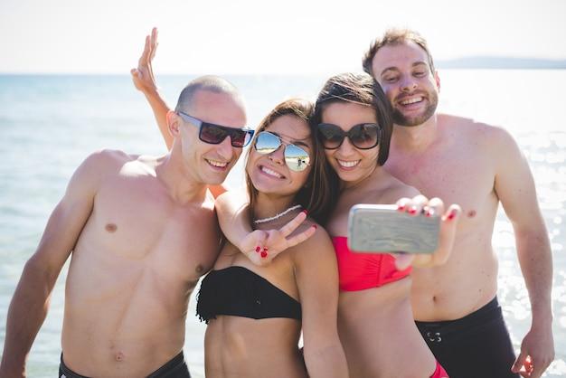 Halve lengte van groep jonge multi-etnische vriendenvrouwen en mannen bij het strand in zomer die selfie nemen