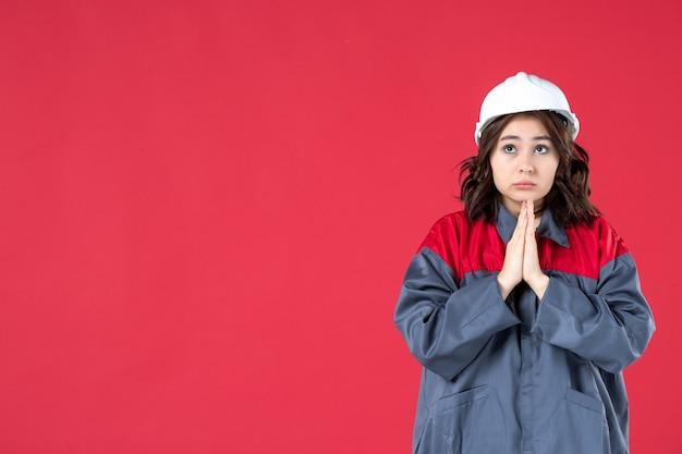 Halve lichaamsopname van denkende vrouwelijke bouwer in uniform met helm en dromen op geïsoleerde rode achtergrond