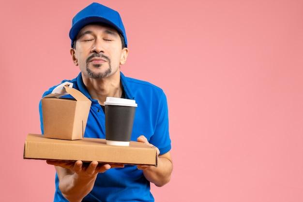 Halve lichaamsopname van een dromerige mannelijke bezorger met een hoed die bestellingen vasthoudt