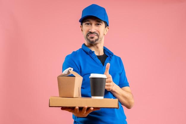 Halve lichaamsopname van een glimlachende, gelukkige mannelijke bezorger met een hoed die bestellingen vasthoudt en een goed gebaar maakt