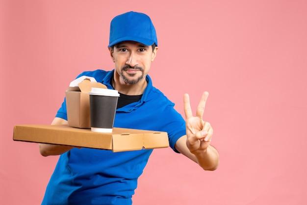 Halve lichaamsopname van een glimlachende mannelijke bezorger die een hoed draagt die bestellingen geeft en een overwinningsgebaar maakt op een pastelkleurige perzikachtergrond