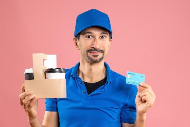Halve lichaamsopname van een glimlachende mannelijke bezorger met een hoed die bestellingen en een bankkaart vasthoudt