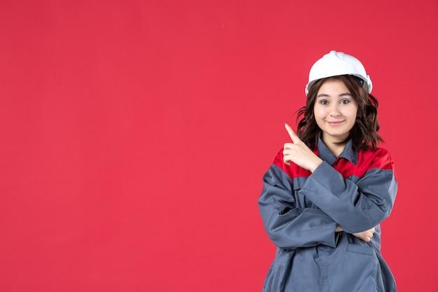 Halve lichaamsopname van een glimlachende vrouwelijke bouwer in uniform met helm en naar boven gericht aan de rechterkant op geïsoleerde rode achtergrond