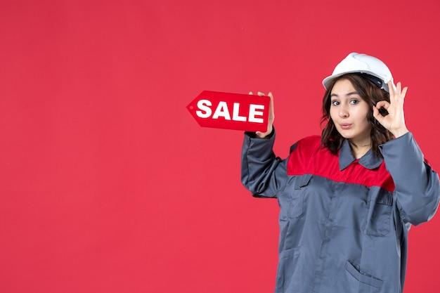 Halve lichaamsopname van een glimlachende vrouwelijke werknemer in uniform die een harde hoed draagt en een verkooppictogram aanwijst dat een brilgebaar maakt op geïsoleerde rode achtergrond