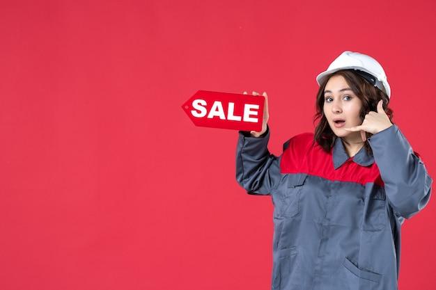 Halve lichaamsopname van een glimlachende vrouwelijke werknemer in uniform met een helm en een wijzend verkooppictogram dat me een gebaar maakt op geïsoleerde rode achtergrond