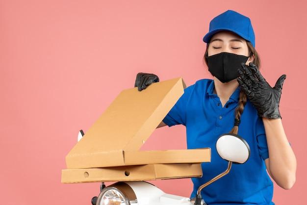 Halve lichaamsopname van een jonge, nieuwsgierige vrouwelijke koerier met een medisch masker en handschoenen die op een scooter zitten die dozen opent op een pastelkleurige perzikachtergrond